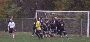 Lake Center Christian's soccer team mobs goalkeeper Caleb Bower after Bower saved a shot by Crestview's Jacob Wickline (6) to win a Div. III district semifinal penalty shootout on Thursday at Crestview High School. Also shown is Crestview goalie Costen Santelmo (green shirt). (Salem News/Michael S. Burich)