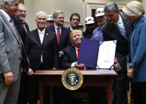 President Donald Trump, joined by coal miners and members of Congress including Sen. Shelley Moore Capito, R-W. Va., right, Sen. Joe Manchin, D-W. Va., second from right, and Rep. Bill Johnson, R-Ohio, third from right, holds up H.J. Res. 38 after signing it in the Roosevelt Room of the White House in Washington, Thursday. (AP Photo)