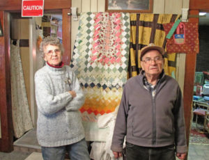 The Hanoverton Curio Shop, owned by Ray and Joyce Carnes has been at the center of Hanoverton for years. They purchased the building 20 years  ago and turned the 10 rooms into display areas loaded with antiques. They are pictured with two special quilts. The quilt on the left was hand-stitched from cotton in 1933 by Mabel Pike and came from the old Fort Tuscarora Museum on state Route 172. The quilt on the right is from Bowling Green, Ohio, and is made of satin with each square hand-stitched, probably from the 1940s.  (Salem News photo by Larry Shields)