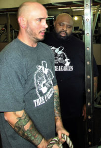 "For two months, former world boxing champion (WBC) Kelly Pavlik of Youngstown and Lonnie TK Atkins of Salem have been working through weight lifting routines at the Salem Community Center. Atkins is Pavlik's personal trainer, a world weightlifting champion and founder of the ""Unbreakables,"" a local powerlifting team that Pavlik sponsors. Atkins is also the former state chairman for the 100 Percent Raw Powerlifting Federation. Pavlik, who said he wanted ""to get stronger on the bench,"" is also transforming his health. In this photo, Atkins guides Pavlik through arm training sets. (Salem News photo Larry Shields)"