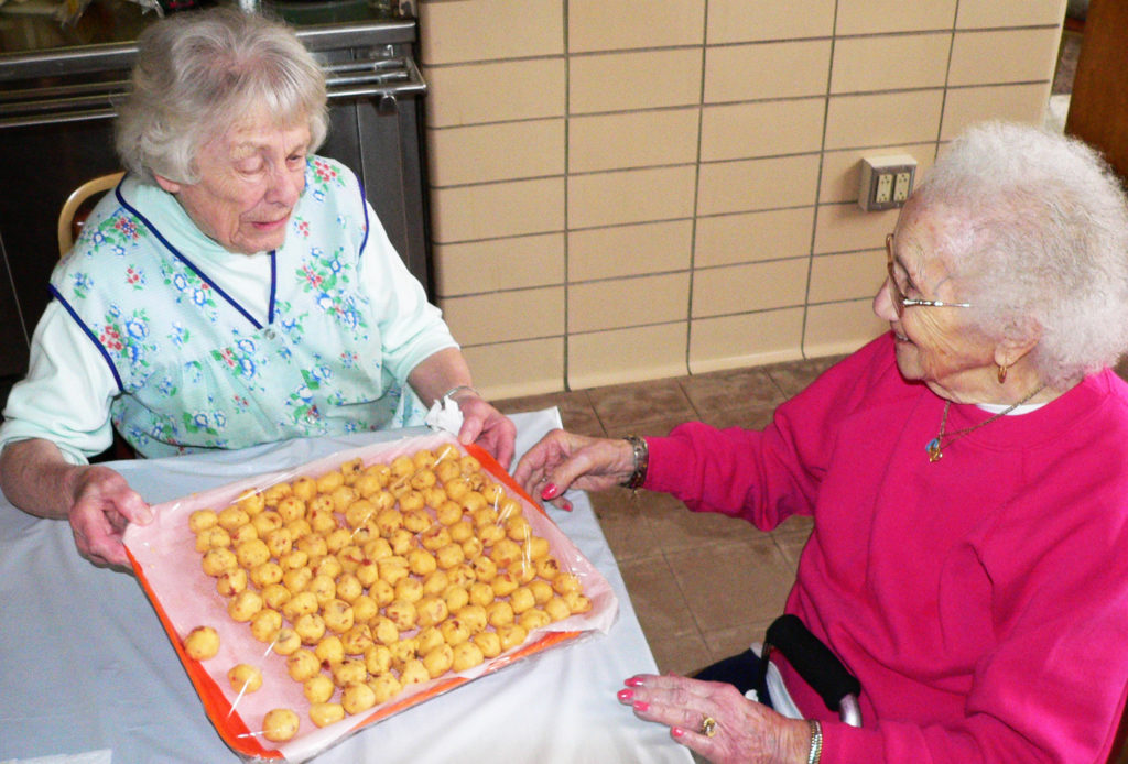 Nora Morelli, 90, left, and Angie Beltempo, 102, are living proof you don't have to slow down in old age. Both women are active volunteers during the St. Patrick Catholic Church pierogi season and are seen finishing a tray of filling Tuesday morning. The sale continues through April 7, with pick up from 1 to 4 p.m. Wednesdays and Fridays, as well as after Mass on Sundays. (Salem News photo by Kevin Howell)