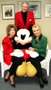 From left, Salem Storybook Museum curator Janis Yereb, former Disney senior artist Richard Theiss and his wife, Hope, gather around a large stuffed Mickey Mouse to promote Mickey at the Museum, a program to salute their Mickey Mouse collections and celebrate  Richard Theiss and his life's work from 7 to 9 p.m. Thursday at the Salem Storybook Museum inside the Kent City Center on North Lincoln Avenue. The display also will be open to the public from 1 to 6 p.m. Saturday. (Salem News photo by Mary Ann Greier)