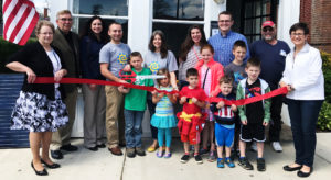 The Columbiana Area Chamber of Commerce held a red-ribbon cutting ceremony on Friday for Energy Optimism LLC. From left, Carol Cobbs, chamber director; Rick Noel, city councilman; Jen Colella, tourism bureau; Charles Hatch, owner; Jonah Hatch; Talia Hatch; Kathryn Hatch; Heather Doyle; Nathan Doyle; Moriah Doyle; Ury Doyle; Elijah Doyle; Isaiah Doyle; Zeke Doyle; Mike Ritterspach; and Ginny Perkins, chamber president. (Submitted photo)