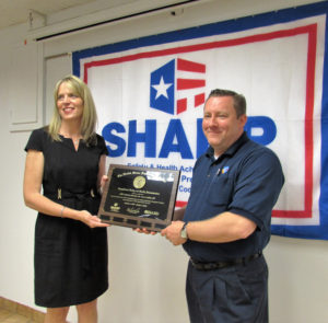 Sarah Morrison, the administrator and CEO of the Ohio Bureau of Workers' Compensation, presents Bruce Parker, production manager for CMI Industry America Inc., with the U.S. Department of Labor, Occupational Safety and Health Administration (OSHA) award for meeting the requirements of the Safety Health Achievement Recognition Program (SHARP) during a Wednesday morning ceremony at the plant, located at 435 W. Wilson Ave. in Salem. (Salem News photo by Larry Shields)
