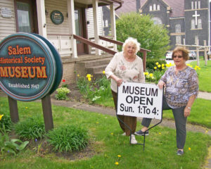 Salem Historical Society members Gloria Judy and Maria Harrold place the sign indicating the opening of the Salem Historical Museum for the 45th season. The museum is open from 1 to 4 p.m. Sundays and 6 to 9 p.m. each third Tuesday May 7 through Oct. 29. (Submitted photo)