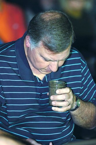 MARK NANCE/Sun-Gazette A Muncy resident smells a sample of engineered pulverized fuel that the proposed waste-to-energy plant will make to sell to power companies to burn to produce energy.
