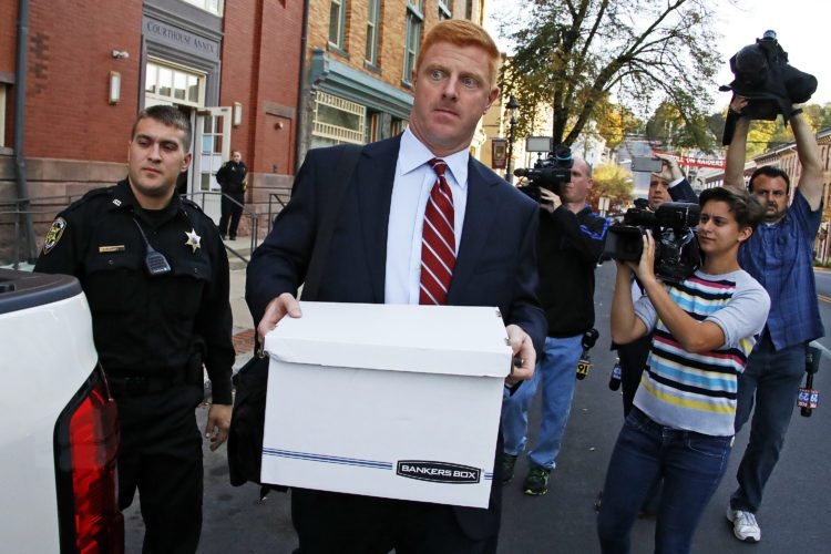 ASSOCIATED PRESS Former Penn State University assistant football coach Mike McQueary, center, leaves the Centre County Courthouse Annex in Bellefonte on Monday.
