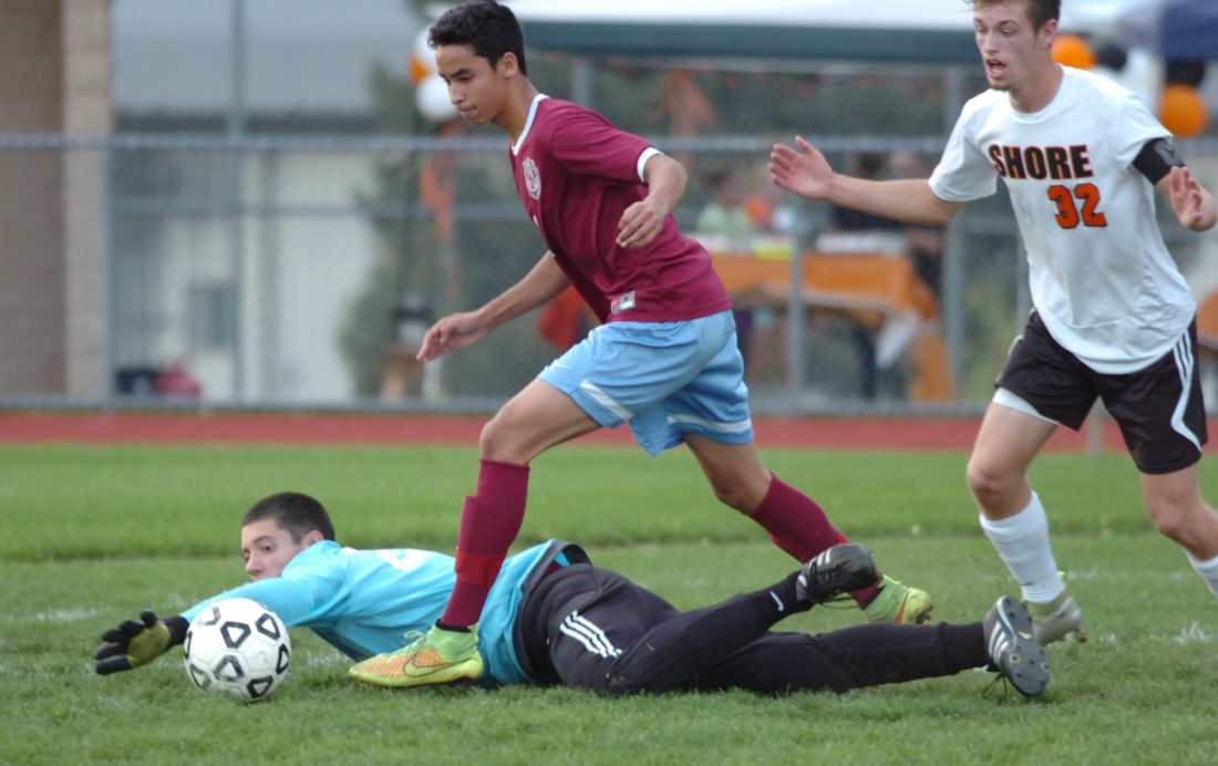 Loyalsock goalkeeper Matt Loeh dives for the ball after colliding with teammate Ilan Quintana and Jersey Shore's Connor Anderson during the first half at Jersey Shore onThursday. MARK NANCE/Sun-Gazette