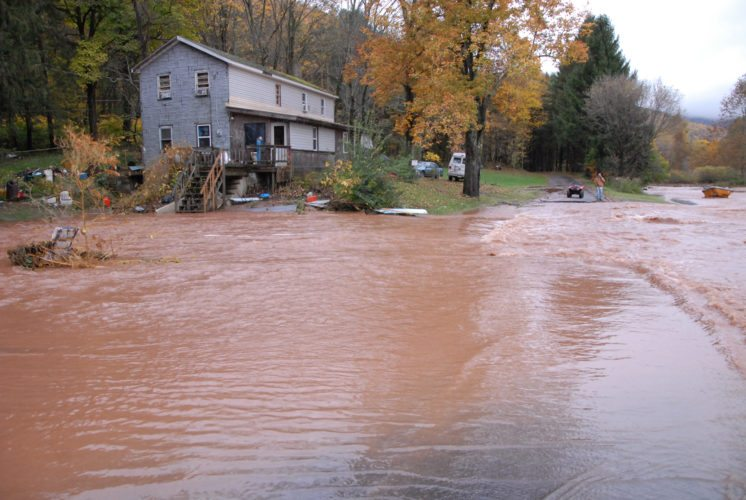 MARK NANCE/Sun-Gazette A home seems stranded as water flows from the mountain over Lower Bodines Road and into a field in Bodines Friday morning. The object on the far right is a hot tub.