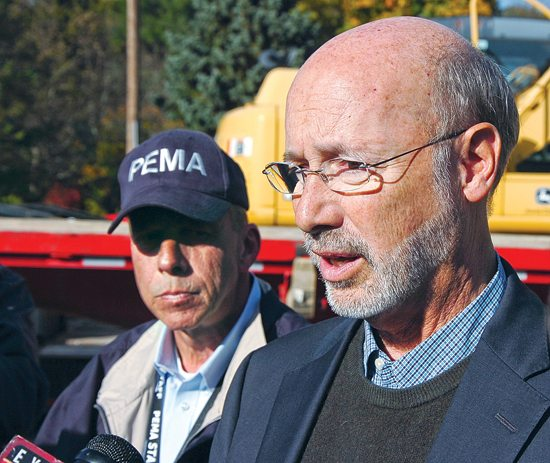 MARK NANCE/Sun-Gazette Pennsylvania Gov. Tom Wolf, right, and Richard D. Flinn Jr., director of the state Emergency Management Agency, left, answer questions from the media after meeting with officials at the Eldred Township Volunteer Fire Co. on Sunday.