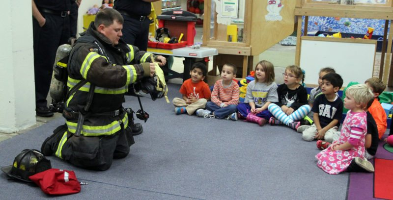 Williamsport Bureau of Fire firefighter Frank Baker puts on his gear to show the Little Lambs Preschool students how it keeps him protected during the visit from Williamsport Bureau of Fire firefighters on Thursday morning at the school in Williamsport. October is FIre Prevention Month. KAREN VIBERT-KENNEDY/Sun-Gazette