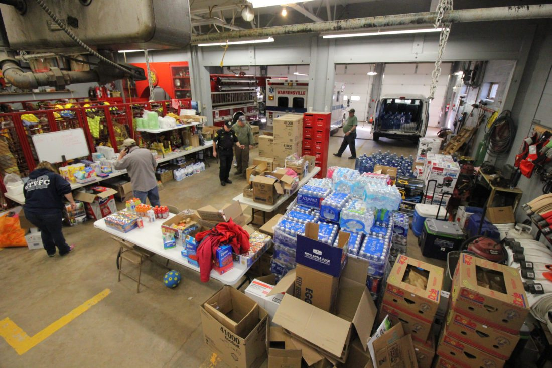 ANNE REINER/Sun-Gazette  Volunteers at the Eldred Township Fire Co. organize and prepare to deliver donations to local residents affected by Friday morning's flash flooding.