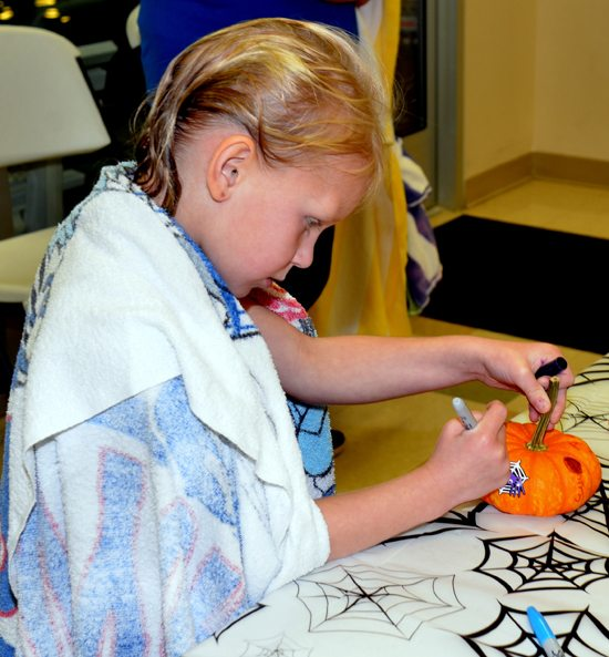 JUDI PINKERTON/Sun-Gazette Correspondent On Oct. 15, the East Lycoming YMCA in Muncy held its first Halloween and Craft Fair that included activities for the entire family. Pictured here, Addilynn Shirvinski, 6, of Hughesville, daughter of Paul Shirvinski, decorates a pumpkin.