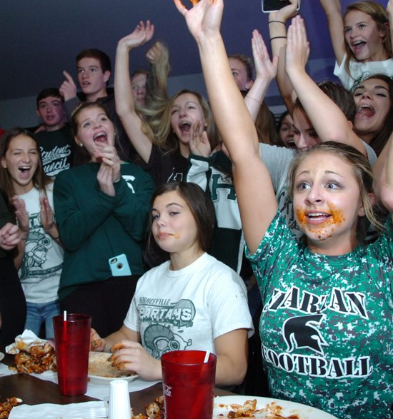 MARK NANCE/Sun-Gazette Hughesville High School cheerleaders junior Missy Walburn, left, sophomore Emilie Dylina, middle, and senior Jackie McClintock, along with Hughesville fans cheer as they win the cheerleaders Pre-Game Wing-Eating Contest at the Log Cabin Inn Muncy Tuesday night. Three cheerleaders from Hughesville and Muncy  along with three football players from each school, faced off against each other, leading up to their annual football match-up on Friday night.