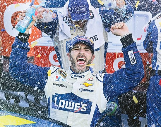 Jimmie Johnson celebrates after winning the NASCAR Sprint Cup Series auto race at Martinsville Speedway in Martinsville, Va., Sunday, Oct. 30, 2016. (AP Photo/Steve Helber)