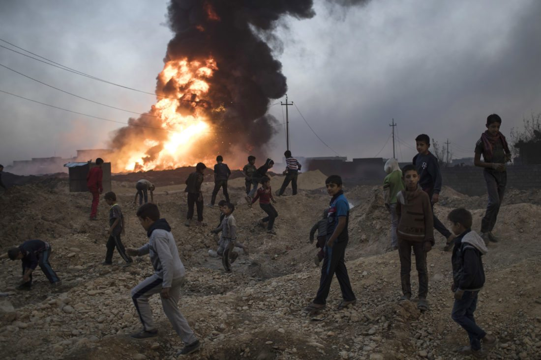 ASSOCIATED PRESS Children play next to a burning oil field in Qayara, Iraq, near Mosul on Thursday. A senior military  commander says more than 5,000 civilians have been evacuated from newly retaken eastern parts of the Islamic State  group-held city of Mosul and taken to camps.