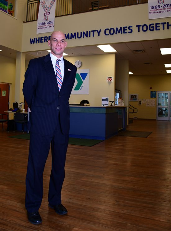 MARK NANCE/Sun-Gazette Chad A. Eberhart, standing in the Williamsport YMCA, has been named the new CEO of the River Valley Regional YMCA.