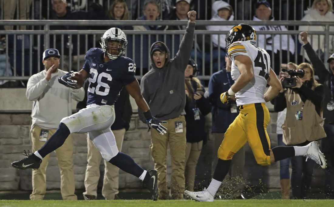 Penn State's Saquon Barkley (26) runs in for a touchdown as Iowa's Bo Bower (41) chases after him during the second half last week vs. Iowa.