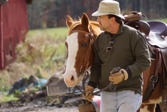 PHOTO PROVIDED Michael Lundy, of Williamsport and 32-year Air Force veteran leads his horse from the barn to the riding arena at during phase one of Woodland View Adventures, Inc.'s new program.