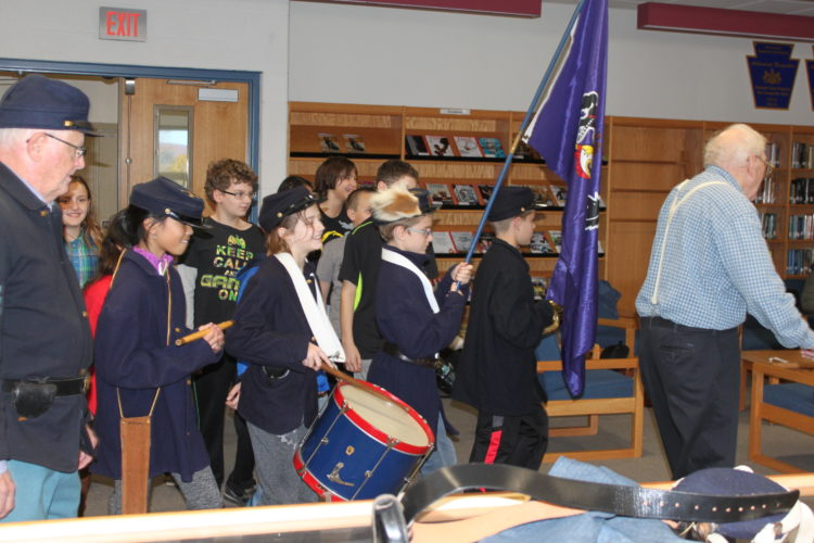 CHERYL R. CLARKE/Sun-Gazette Miller Elementary fifth-grade students march around the North Penn Mansfield High School library as part of Remy's presentation at their school. Providing assistance at below left is Larry Crane, of Tioga.