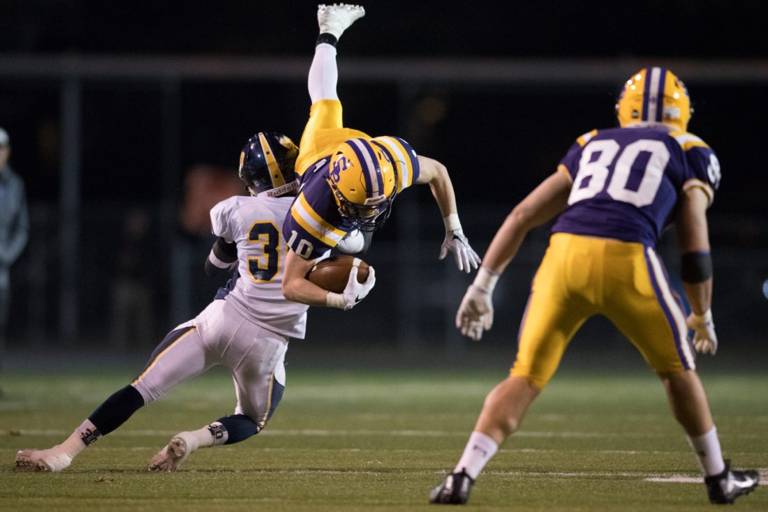 Scranton Prep's Tom Doherty goes up in the air on a tackle by Montoursville's Nolan Ott during a PIAA Class AAA playoff game at Wyoming Valley West Stadium in Kingston on Friday, Nov. 18, 2016. Christopher Dolan / Staff Photographer