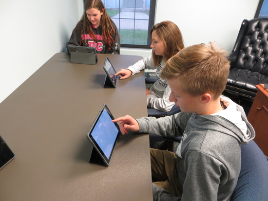 CARA MORNINGSTAR/Sun-Gazette Students look at the new Muncy School District app on iPads at Muncy Jr. Sr. High School. From left, Abbey Millard, ninth grader, Sehya Moyer, tenth grader and Jacob Hill, ninth grader.