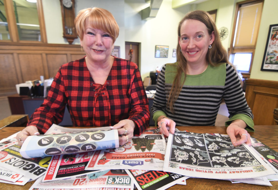 MARK NANCE/Sun-Gazette Linda Neupauer, left, classified advertising manager, and Beth Miller, advertising sales representative, look through Thursday's paper with all its ads for Black Friday.