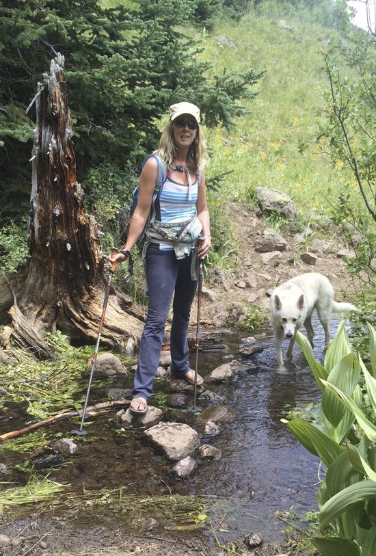 This undated photo shows Dagny McKinley and her dog Alma May at Mandall Creek in Colorado. McKinley, an author, blogger and photographer, is one of a number of Americans who has sometimes chosen to spend major holidays alone, as a way of decompressing from busy lives, relaxing and reflecting. Her routine on a birthday, Christmas or Thanksgiving spent solo often includes a hike with her dog. (Tom Thurston via AP)