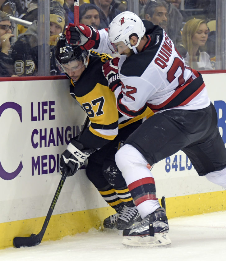 New Jersey Devils defenseman Kyle Quincey (22) checks Pittsburgh Penguins center Sidney Crosby (87) during the second period of an NHL hockey game on Saturday, Nov. 26, 2016, in Pittsburgh. (AP Photo/Fred Vuich)