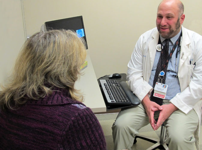PHOTO PROVIDED Dr. David Bulbin talks with a patient recently at his office in Geisinger Medical Center in Danville. The rheumatologist says the coming of cold and/or wet weather often can cause those suffering with arthritis to feel more pain.