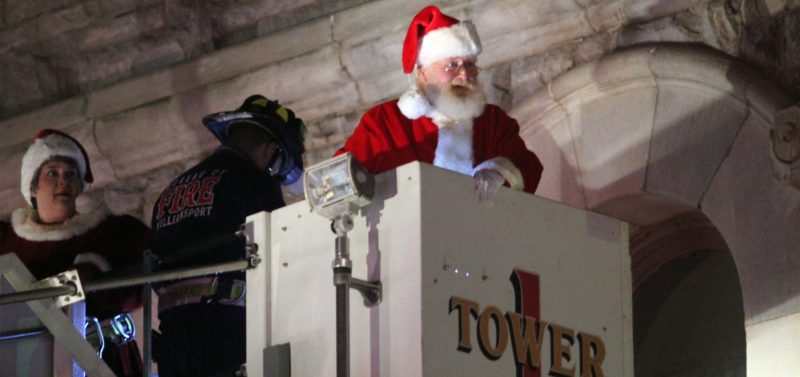KAREN VIBERT-KENNEDY/Sun-Gazette Santa and Mrs. Claus make their arrival from the balcony of City Hall courtesy of the Williamsport Bureau of Fire's Tower One during the Mayor's Annual Tree Lighting presented by the city of Williamsport on Friday night.