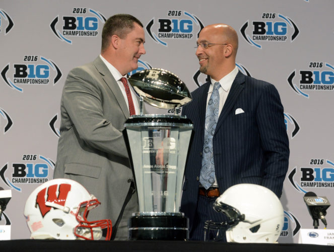 Wisconsin coach Paul Chryst and Penn State coach James Franklin shake hands next to the Big Ten championship trophy in Indianapolis on Friday during a press conference. The Badgers and Nittany Lions play tonight for the conference title. (PAT WAKSMUNSKI/For The Sun-Gazette)