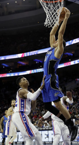 Orlando Magic's Aaron Gordon, right, goes up for a dunk against Philadelphia 76ers' Richaun Holmes during the first half of an NBA basketball game, Friday, Dec. 2, 2016, in Philadelphia. (AP Photo/Matt Slocum)