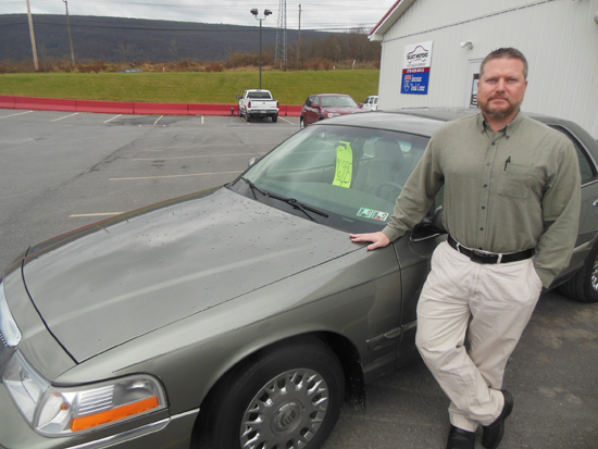MIKE REUTHER/Sun-Gazette Mike Rosamilia shows off a car for sale on the lot at Select Motors on Eye Center Lane.