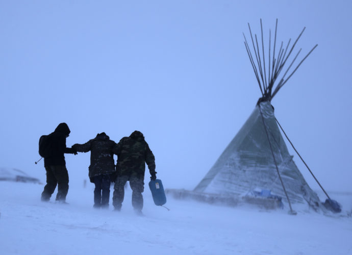 ASSOCIATED PRESS People walk along a snowy hillside in a storm at the Oceti Sakowin camp, where people gathered Monday to protest the Dakota Access oil pipeline in Cannon Ball, N.D. Many pipeline opponents who've gathered for months in the camp in southern North Dakota are committed to staying despite wintry weather and demands that they leave.