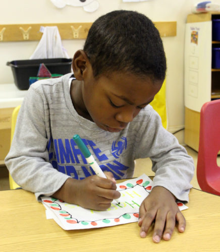 KAREN VIBERT-KENNEDY Sun-Gazette Preschool students work on their holiday cards for troops deployed overseas in their classroom at the YMCA Child Care Center in Randall Circle in Loyalsock Township on Wednesday morning. Around 40 preschool and afterschool  students ages 3-12 years old have been making the cards. According to teacher Chelsea Walburn, the cards give the students the opportunity to not only practice their handwriting skills but also to learn that not everyone gets to spend the holidays with their families.