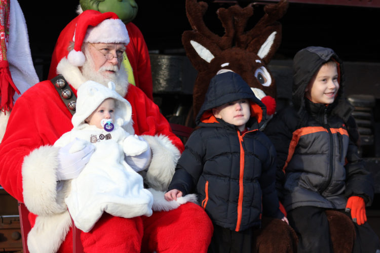 ANNE REINER/Sun-Gazette  Kayla Daugherty, 1, Carson Daugherty, 3, and Gaven Daugherty, 6, sit with Santa outside the North Shore Railroad train at its Maynard Street stop Saturday after a Polar Express Train Excursion. Excursions continue today at noon, 2, 4 and 6 p.m. Tickets are on  sale at the Williamsport/Lycoming Chamber of Commerce Visitor's Center, which is open 11 a.m to 3 p.m.