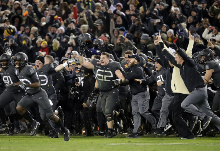 Army players and coaches run onto the field after defeating Navy, 21-17, in Baltimore on Saturday.