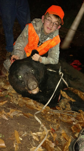 "PHOTOS PROVIDED Charlie Pittenger, 15, of New Columbia, shows off his first black bear, which he shot on the first day of rifle deer season last month. When he and his dad headed into the woods that day, Charlie was hoping to bag his first buck. Harvesting the bear instead still ""was a special thing,"" Charlie said, even though the meat was inedible due to an infection."