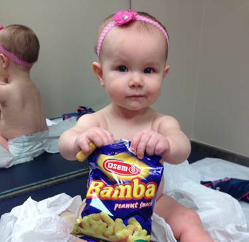 ASSOCIATED PRESS In this photo provided by the Carrie Stevenson, her daughter Estelle holds a bag of peanut snacks in her pediatrician's office at age 9 months, in Columbus, Ohio.