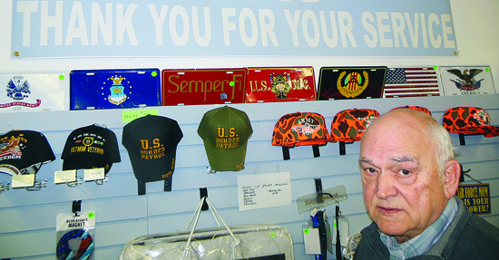 MIKE REUTHER/Sun-Gazette Butch Bradley displays hats for the branches of military service sold at By-4-Les, his Old Lycoming Township store.