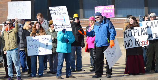 PAT CROSSLEY/Sun-Gazette Correspondent A crowd hoists signs depicting their opinions about a proposed plan to do away with the Affordable Care Act.