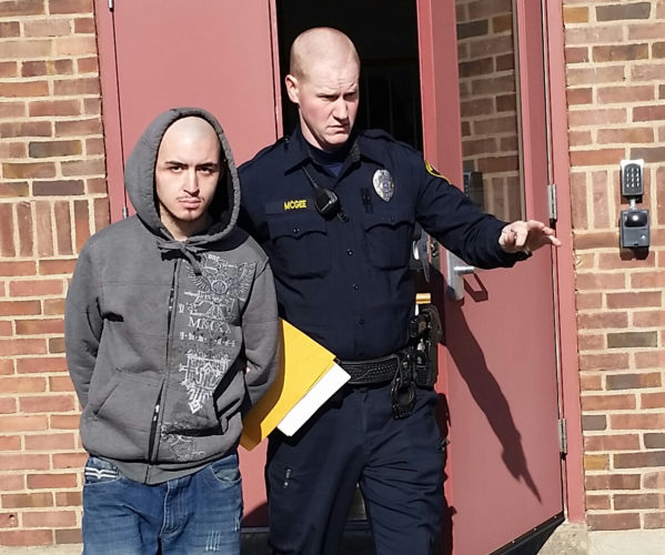 PHILIP A. HOLMES/Sun-Gazette Williamsport Patrolman Brian McGee takes convicted felon Tanner John Blanksby to the Lycoming County Prison after the 23-year-old city man was arraigned Monday morning on charges of allegedly stealing two handguns and ammunition last month from his father's home in the city.