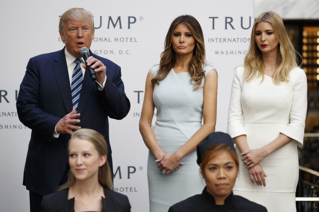 ASSOCIATED PRESS In this Oct. 26, 2016 file photo, Ivanka Trump, right, and Melania Trump, center, listen as then-Republican presidential candidate Donald Trump speaks during the grand opening of the Trump International Hotel-Old Post Office in Washington. People across the globe are always fascinated by what the incoming U.S. first lady is wearing to the inauguration. This time, as never before, the question is interlaced with politics, as designers have publicly grappled with the question of whether they would dress Melania Trump. Questions have also been raised about Ivanka Trump and her own label.