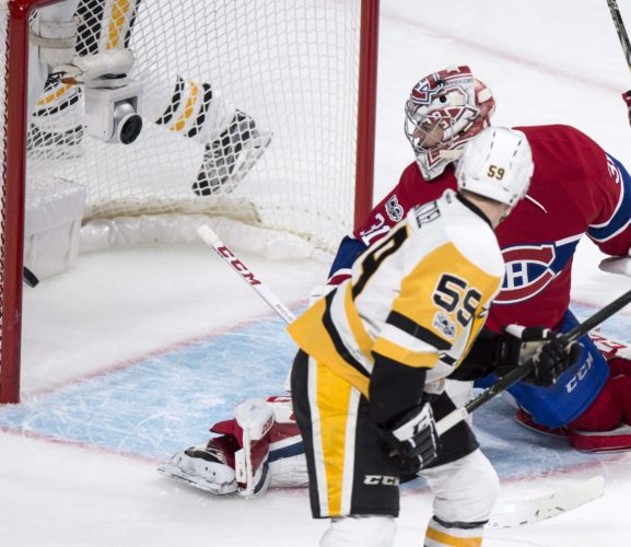 Pittsburgh Penguins' Jake Guentzel deflects the puck to score past Montreal Canadiens goalie Carey Price during the second period of an NHL hockey game, Wednesday, Jan. 18, 2017 in Montreal. (Paul Chiasson/The Canadian Press via AP)