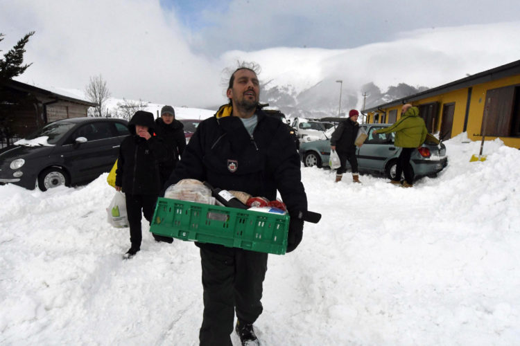 ASSOCIATED PRESS Residents on Thursday carry food and goods brought by Italian army vehicles in the village of Campotosto in the mountainous region of central Italy that has been struck by a series of quakes since August that destroyed historic centers in dozens of towns and hamlets.