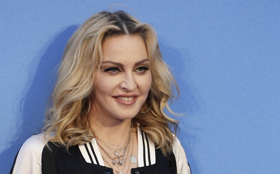 "In this Sept. 15, 2016 file photo, Madonna poses for photographers upon arrival at the World premiere of the film ""The Beatles, Eight Days a Week"" in London. Madonna is trying to put a positive spin on President-elect Donald Trump's Friday, Jan. 20, 2017, inauguration. The superstar spoke at the Brooklyn Museum Thursday night, Jan. 19, with artist Marilyn Minter about art in a time of protest, among other things."