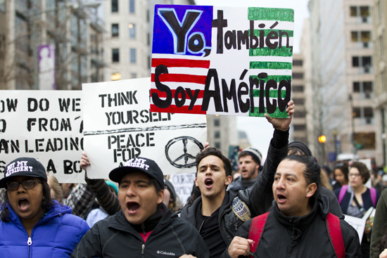 Demonstrators march on the street near a security checkpoint inaugural entrance, Friday, in Washington, ahead of President-elect Donald Trump's inauguration.