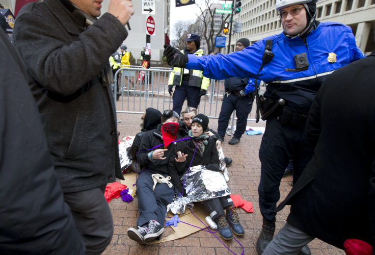 ASSOCIATED PRESS Demonstrators sit at one of the entrance as police officer let people pass let to the inauguration in Washington on Friday ahead of the inauguration.