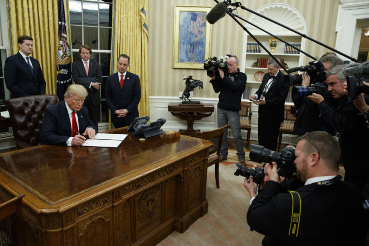 President Donald Trump signs his first executive order Friday in the Oval Office of the White House.
